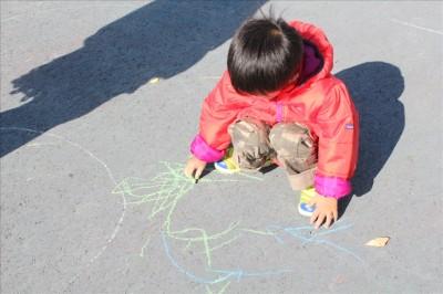 アスファルト地面へチョークでお絵かきの2歳児