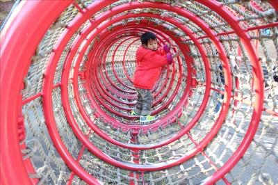 網のトンネルを潜る2歳児