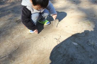 広場でお絵かきする幼児