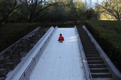ジャンボ滑り台を滑る幼児