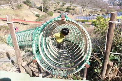 網のトンネルの出口を出る3歳児