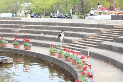 噴水広場の周りを走って遊ぶ3歳児