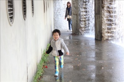 滝の中を走り抜ける3歳児