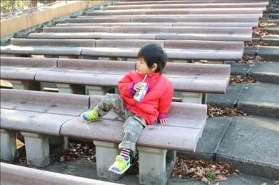 野外音楽堂の観客席でくつろぐ3歳児