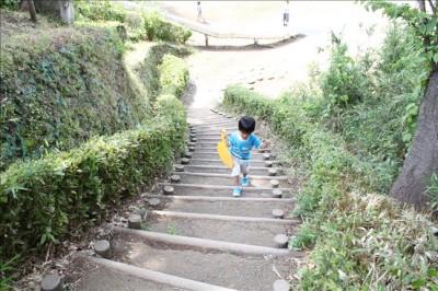 ロング滑り台の出発点へ階段を登る幼児の姿