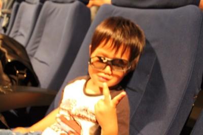 映画館内で3Dメガネをかけて映画が始まるのを待つ3歳児