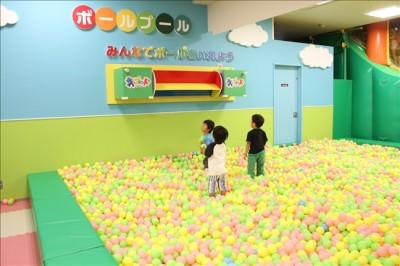 キッズランドのボールプールでボール遊びをする幼児たち