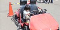 ゴーカート乗り場の前にある展示用の赤いゴーカートに乗る息子のペン太