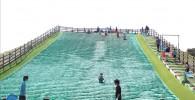 大きな芝ソリゲレンデで遊ぶ子供たちの様子