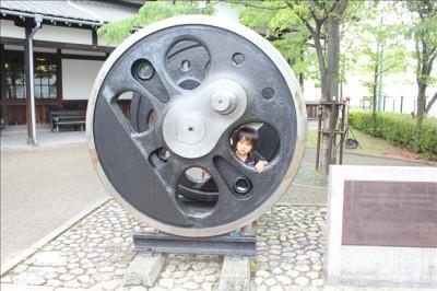 蒸気機関車館入り口前に展示してある蒸気機関車の大きな車輪で遊ぶ3歳児