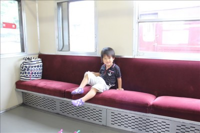 展示されている古い電車内の客席に座る息子ペン太3歳
