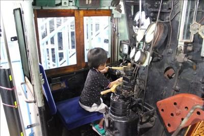 扇形車庫内の蒸気機関車の操縦席に乗る息子のペン太