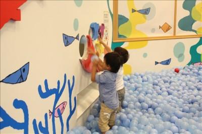 ボールを穴に入れて遊ぶ3歳児