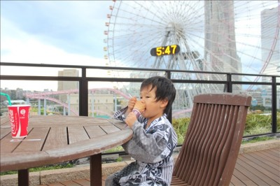 万葉倶楽部9Fの屋外のデッキでソフトクリームを食べる3歳児