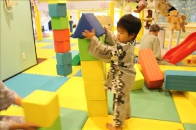 キッズルームのフワフワな積み木のコーナーで遊ぶ3歳児