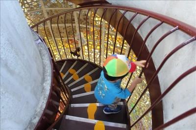 タワーの螺旋階段を上っていく幼児