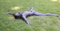 芝生にうつぶせに寝る人の彫刻