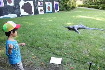 うつぶせの彫刻に興味深々の3歳児