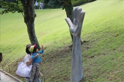 大きな手のひらの彫刻に触りたがる3歳児