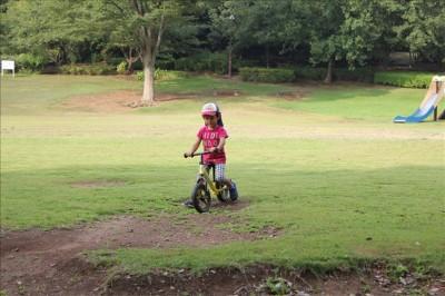 広場でストライダーを楽しむ幼児