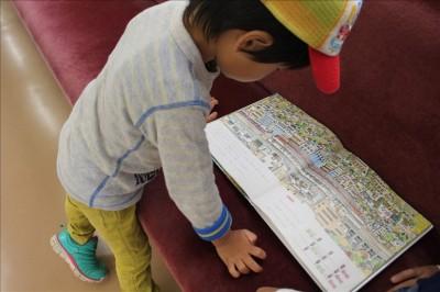 車内に置いてある絵本を見る3歳児