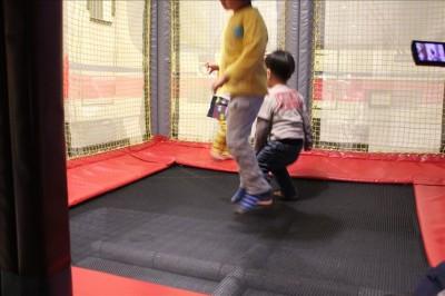 屋内のトランポリンで遊ぶ幼児