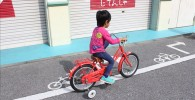 赤い補助輪付き自転車に乗る3歳の息子