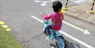 青い補助輪自転車を運転する幼児の後ろ姿