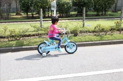ミニSLの線路に沿って自転車で走る息子
