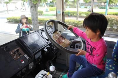 古い都電バスの運転席でハンドルを握る子供