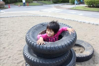 積み上げられたタイヤの中に入って喜ぶ子供