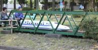 緑の鉄橋を通過するミニ新幹線