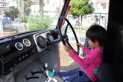 消防車の運転席でハンドルを握る幼児