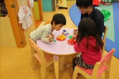 テーブルでママごとをする子供たち
