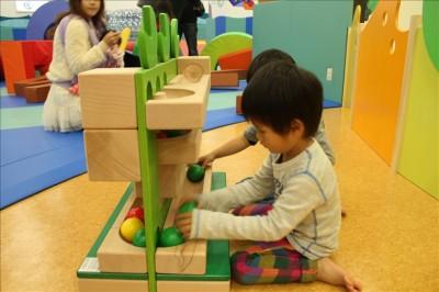 木のボールを転がして遊ぶ大きなおもちゃ