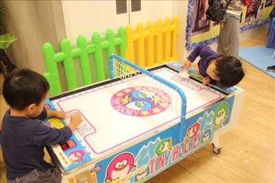 エアホッケーで遊ぶ幼児たち
