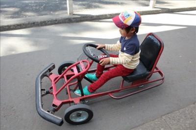 赤い足漕ぎゴーカートで遊ぶ3歳の幼児