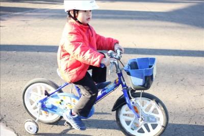 補助輪付き自転車に乗る息子
