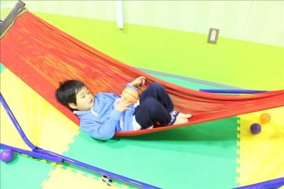 室内スペースのハンモックで寝る児童