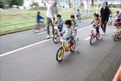 交通公園の補助輪付き自転車に乗る幼児