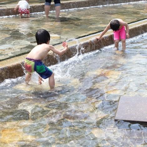 郷土の森博物館のじゃぶじゃぶ池で遊ぶ児童たち