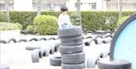 積み上げられたタイヤで遊ぶ子供