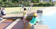 フラワーガーデンの水遊び場で遊ぶ児童