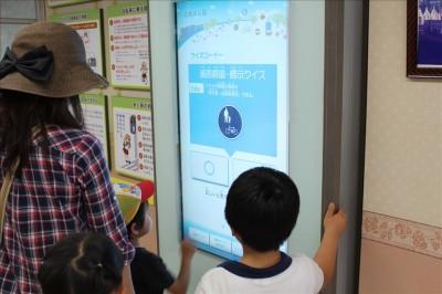 展示室の大型モニタでクイズする子供たち