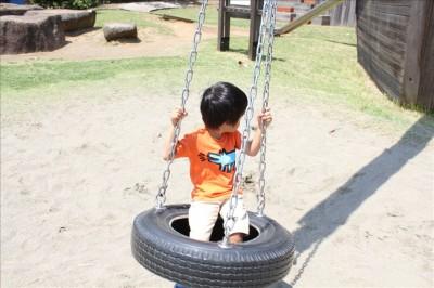 タイヤブランコで遊ぶ児童