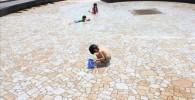 噴水広場のじゃぶじゃぶ池で遊ぶ幼児