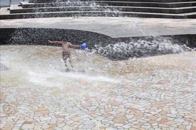 勢い良く出る水を浴びる子供