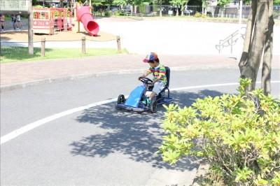 足踏みゴーカートでコースを運転する幼児