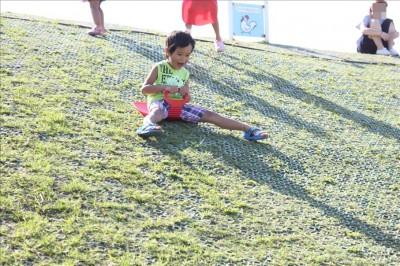 海風公園の芝ソリで遊ぶ子供
